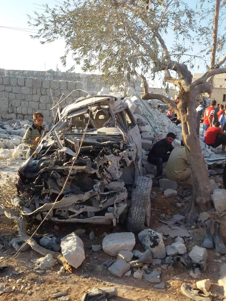 A Syrian boy examines a car destroyed in Tuesday's airstrikes. Coalition aircraft and Tomahawk missiles struck 22 targets used by Islamic State and Khorason forces.
