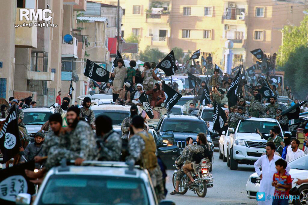 In this undated image posted on June 30, 2014, by the Raqqa Media Center of the Islamic State group, which has been verified and is consistent with other AP reporting, fighters from the Islamic State group parade in Raqqa, north Syria.