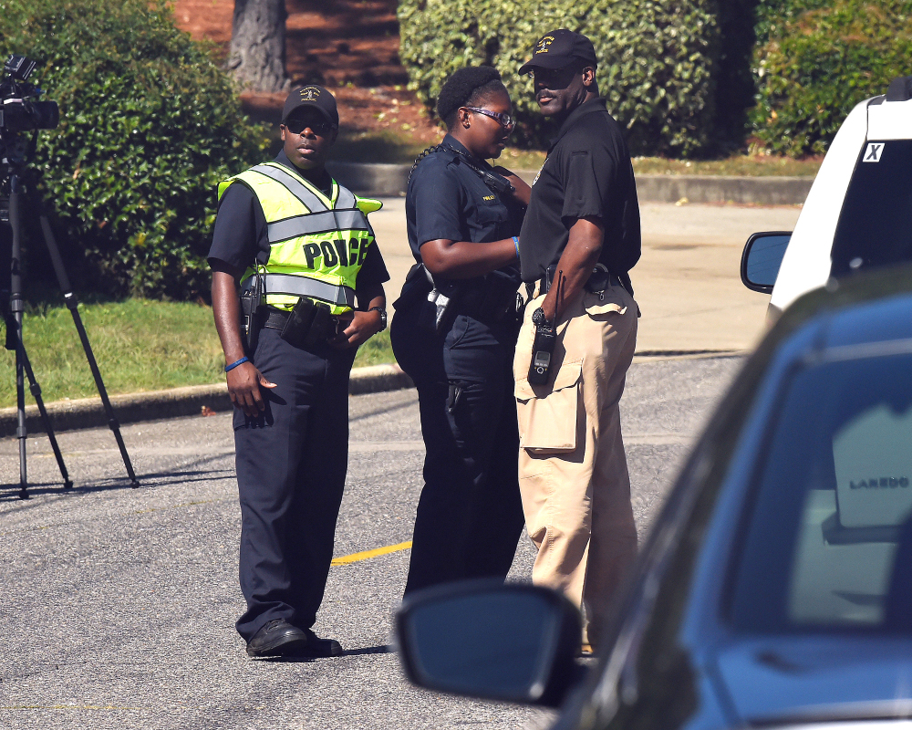Police officers confer near the scene where three people were killed, including the gunman, at a UPS facility in Birmingham, Ala., on Tuesday.