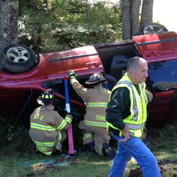 Windsor and Augusta firefighters prepare to extricate one of two women trapped in a van that rolled over Monday on Route 17 in Windsor. Police said Tuesday the driver is likely to face charges.