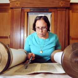 Rabbi Erica Asch checks her position in the text as she rolls a Torah scroll Tuesday in preparation for Rosh Hashanah services at Temple Beth El in Augusta. She pre-positioned the temple's four Torahs so they'd be ready for readings during this week's high holy days services.