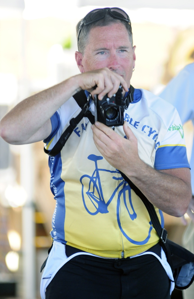 Glenn Charles looks over the top of his camera while photographing speakers Tuesday during an event at the farmers market at Mill Park in Augusta. He is on a bicycle tour to learn about food in New England.