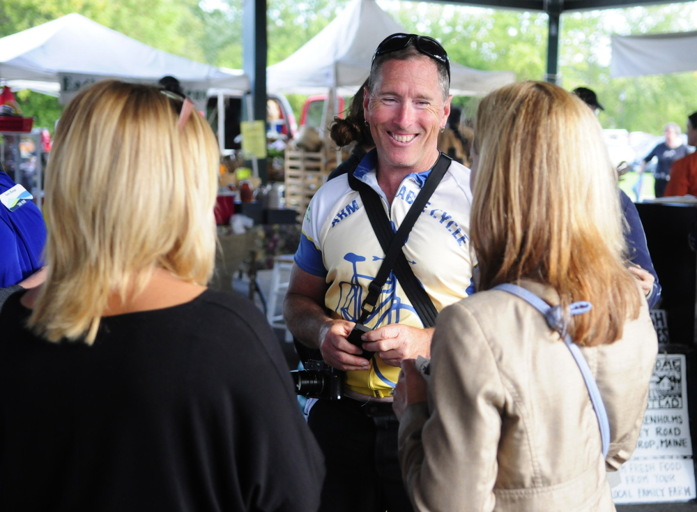 Glenn Charles chats with marketgoers Tuesday during an event at the farmers market at Mill Park in Augusta. He is on a bicycle tour to learn about food in New England.