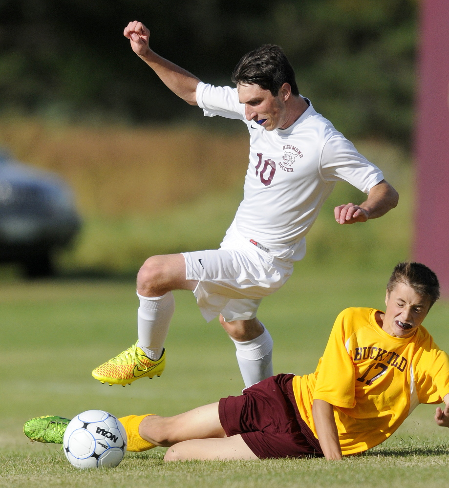 Richmond High School junior Tyler Soucy, left, leaps to avoid Buckfield defender Sidney Jackson during a Western D boys soccer game Tuesday. The Bobcats prevailed 2-1.