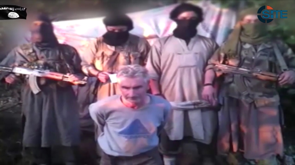 In this still image from video posted on the Internet on Wednesday by a group calling itself Jund al-Khilafah, Soldiers of the Caliphate, members of the group stand behind French mountaineer Herve Gourdel just before beheading him. In the video, the men pledge their allegiance to the leader of the Islamic State group, Abu Bakr al-Baghdadi, before killing Gourdel, 55, whom they abducted on Sunday.
