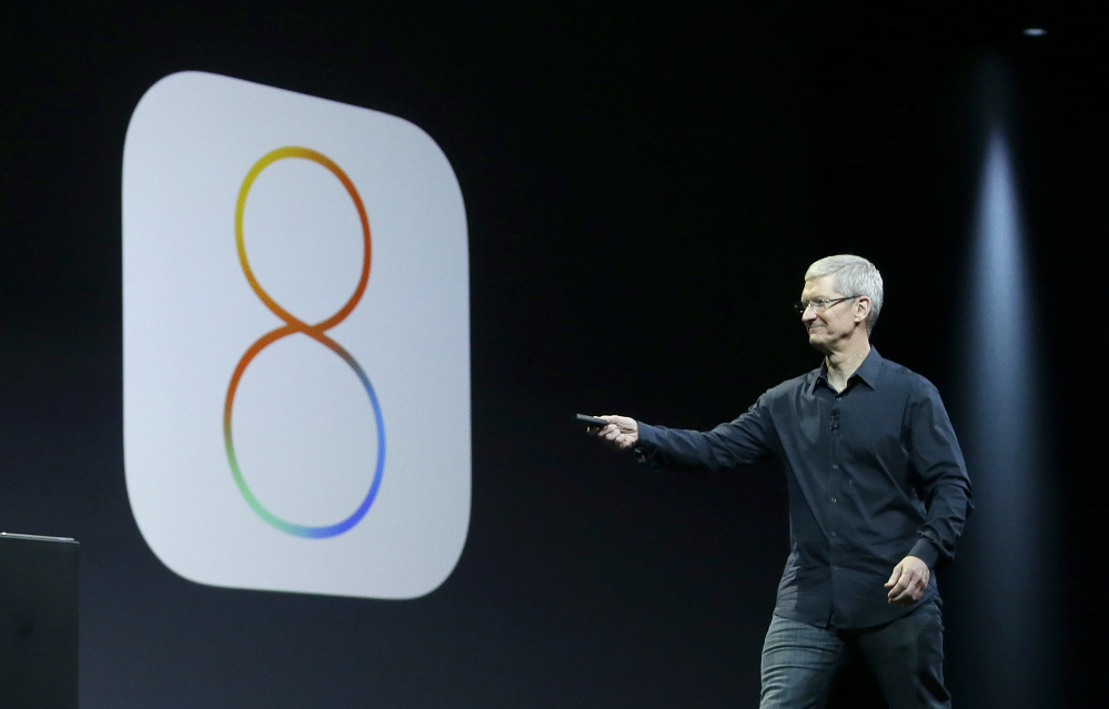 Apple CEO Tim Cook speaks about iOS 8 in June. Apple stopped providing an update to its new iOS 8 mobile operating software Wednesday after getting complaints.