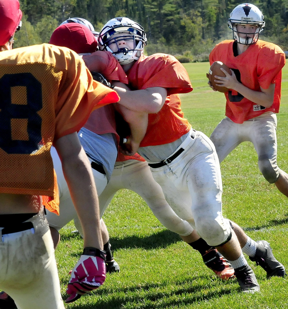 Skowhegan Area High School football player Gus Benson, center, blocks during during practice on Wednesday. Benson, a linebacker on defense, has 58 tackles in three games.