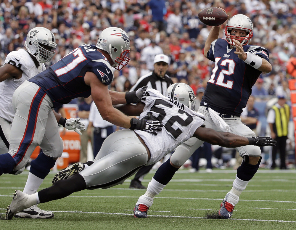 Oakland Raiders outside linebacker Khalil Mack (52) pressures New England Patriots quarterback Tom Brady in the first half Sunday in Foxborough, Mass. The Patriots won 16-9.