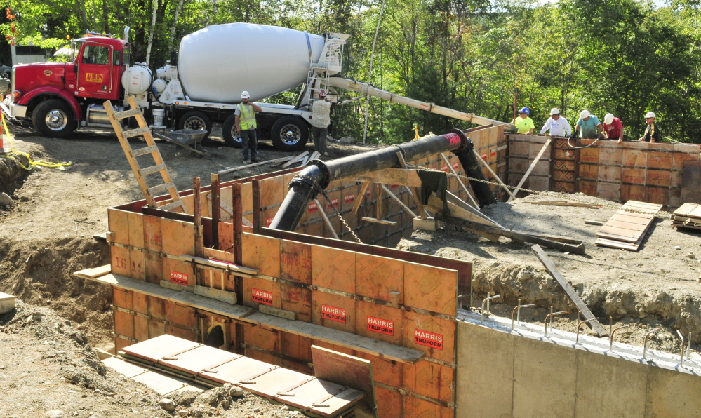 Workers pour the concrete foundation for the new water treatment building being constructed at the Greater Augusta Utilities District's new east side well complex off Riverside Drive in Augusta.