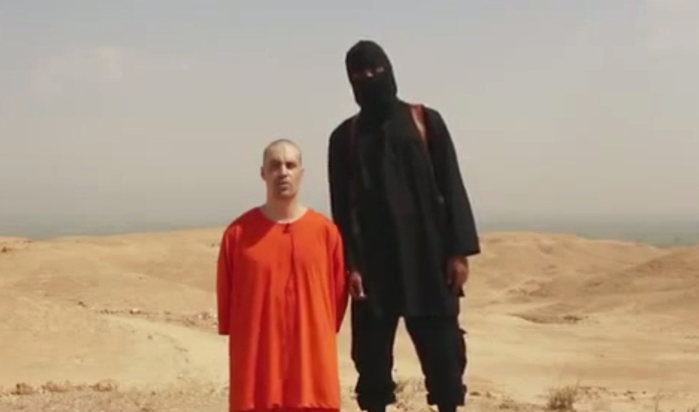 This frame from a video shows American journalist James Foley and a British-accented masked man whom the FBI says it may have identified.