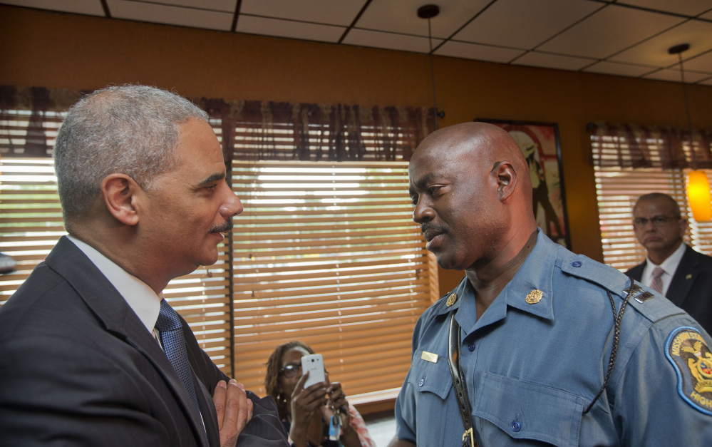 Attorney General Eric Holder speaks with Capt. Ron Johnson of the Missouri State Highway Patrol on Aug. 20 in Ferguson, Mo., where protests raged after a Ferguson police officer shot 18-year-old Michael Brown.
