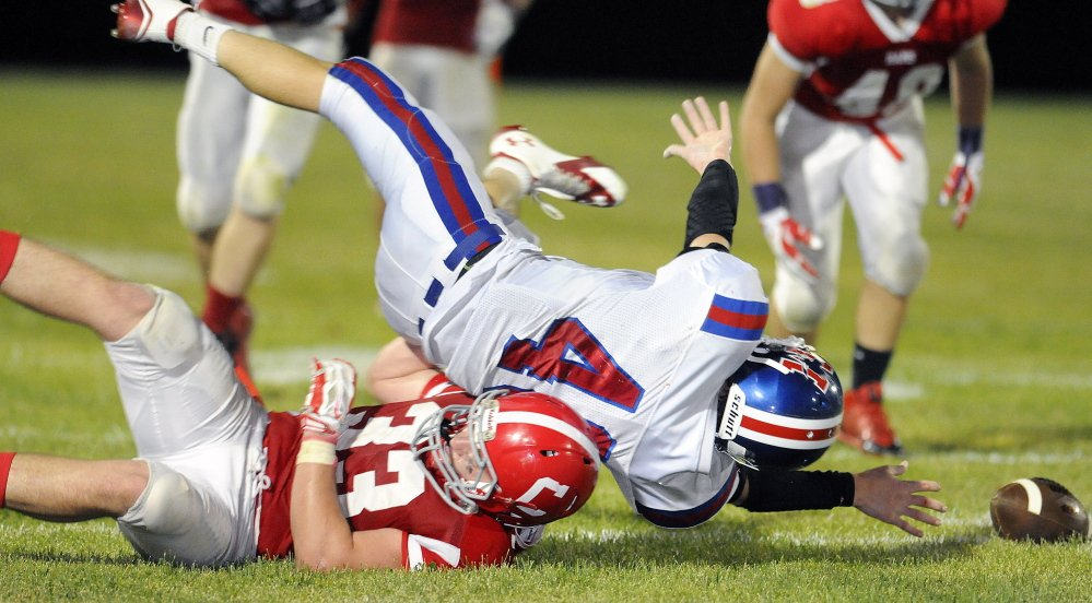 Staff file photo by Andy Molloy  Cony linebacker Reid Shostak (33), hauls down a Messalonskee running back Caleb Chavarie during a Pine tree Conference Class B game earlier this season. Shostak and Rams venture to Keyes Field tonight for a game against Lawrence.