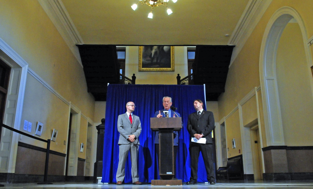 From left, Ben Grant, chairman of the Maine Democratic Party, Rep. Richard Farnsworth, D-Portland, and Sen. Troy Jackson, D-Allagash, take part in a news conference Thursday outside the governor's office in the State House Hall of Flags.