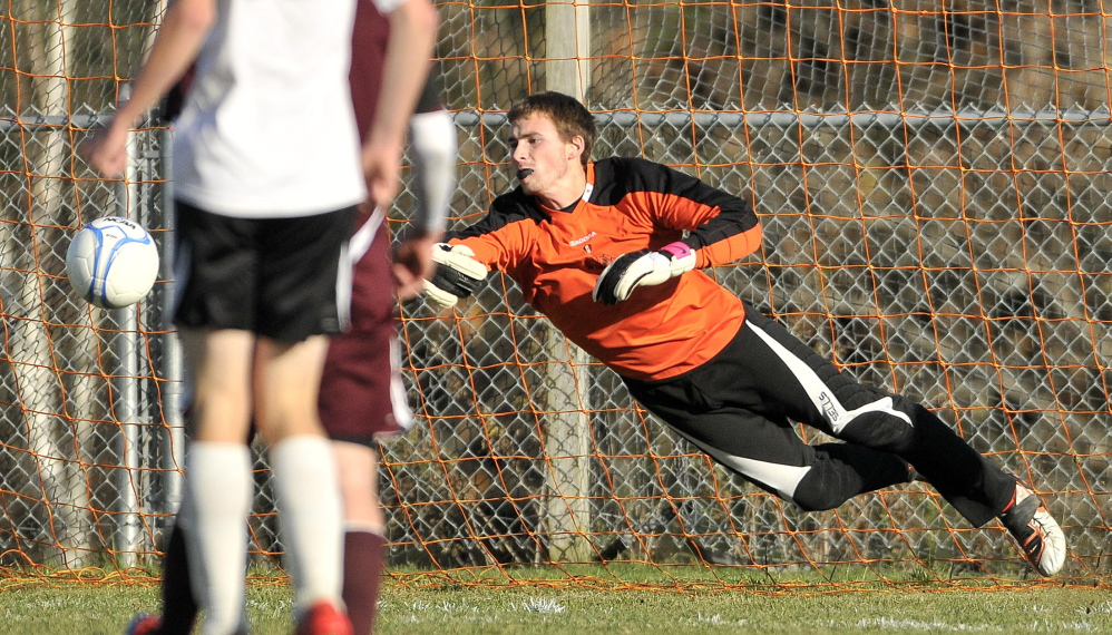 Winslow High School goalie Alex Berard dives to try and stop a shot during a game against Foxcroft last year. Berard, a senior, had a 10-game shutout streak last season for the Black Raiders.