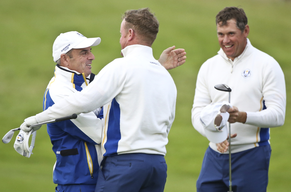 Europe team captain Paul McGinley congratulates Jamie Donaldson and  Lee Westwood, right, on the 17th green after winning  the foursomes match on the second day of the Ryder Cup golf tournament, at Gleneagles, Scotland, on Saturday.