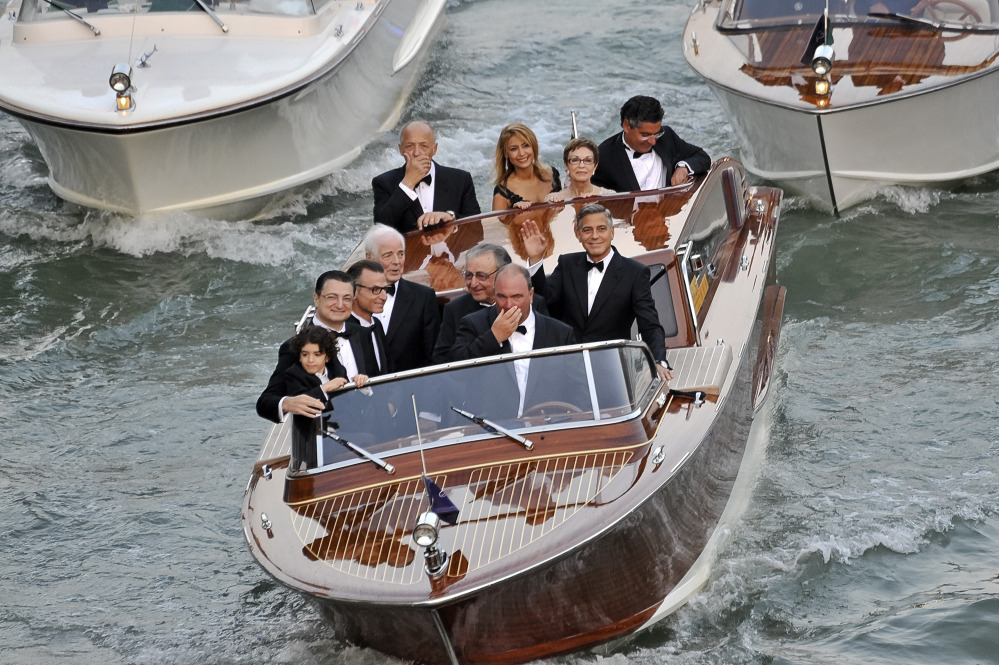 Actor George Clooney, right, waves from a boat with Ramzi Alamuddin, third from right front row, father of her fiancee Amal Alamuddin, his father Nick Clooney, fourth from right front row, and his mother Nina Bruce, second from right back row on their way to the Aman hotel ahead of his wedding in Venice, Italy, on Saturday.