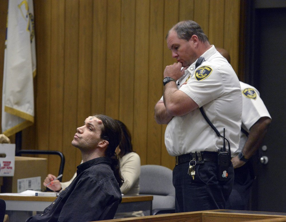 Caius Veiovis, seated, reacts to guilty verdicts in his triple murder trial in Hampden Superior Court Friday in Springfield, Mass. Veiovis is the third of three defendants charged with the 2011 killings of David Glasser, Edward Frampton and Robert Chadwell, of Pittsfield, Mass.