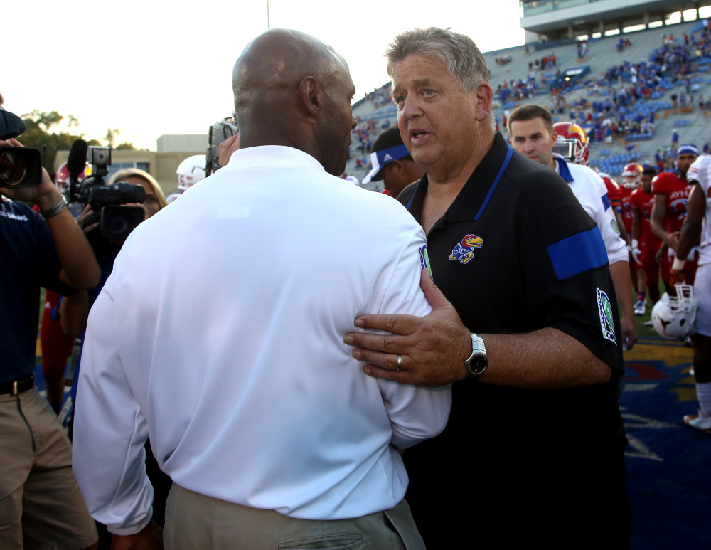 Texas Coach Charlie Strong, front, and Kansas Coach Charlie Weis meet on the field after an NCAA football game on Saturday in Lawrence, Kan. Texas won 23-0. Weis was fired on Sunday.