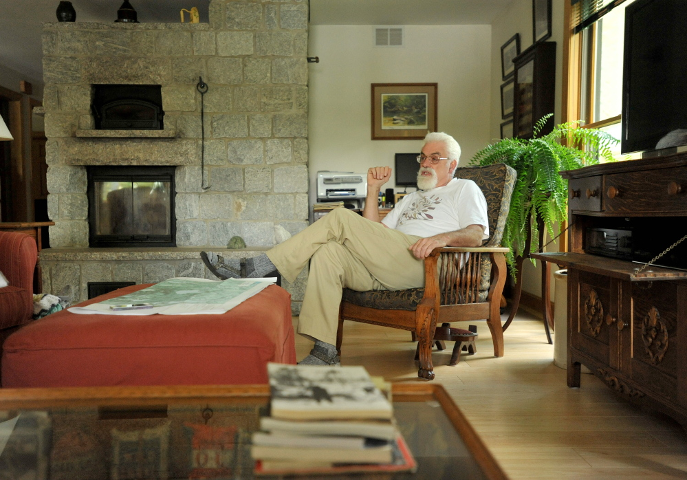 Craig Dickstein, of The Forks, sits in the living room of his home which is divided by the town line of Caratunk and The Forks. Dickstein is part of an effort for Pleasant Pond to secede from The Forks and become part of Caratunk.