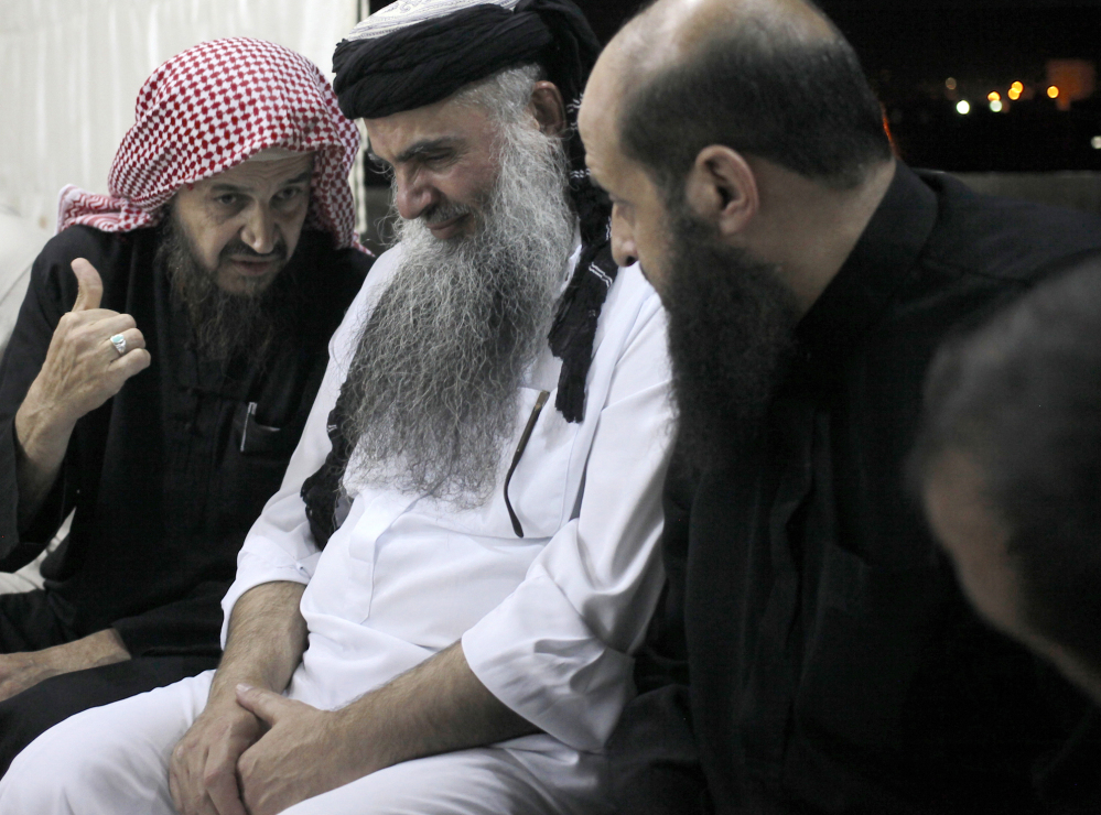 In this Wednesday, Sept. 24, 2014 photo, Radical al-Qaida-linked preacher Abu Qatada, second right, listens to the renowned jihadi ideologue, Abu Mohammed al-Maqdisi, left, on the day Abu Qatada was released from a Jordanian prison after an acquittal on security charges, in Amman, Jordan. Abu Qatada and al-Maqdisi have denounced some of the Islamic State group's practices as un-Islamic.