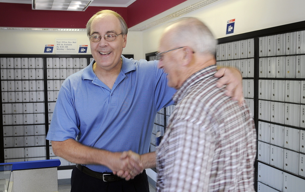 David Shepherd, left, is congratulated Monday by customer Dick Poulin on his retirement from the East Winthrop Post Office. Shepherd is retiring Tuesday after a 35-year postal career.