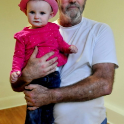 Land raffle winner Orrin Fitzgerald holds 18-month-old Amelia Brown who picked the winner in the Canaan Farmer's Hall raffle to raise money for an elevator. Fitzgerald won a 1.28-acre plot of land on Hinckley Road.