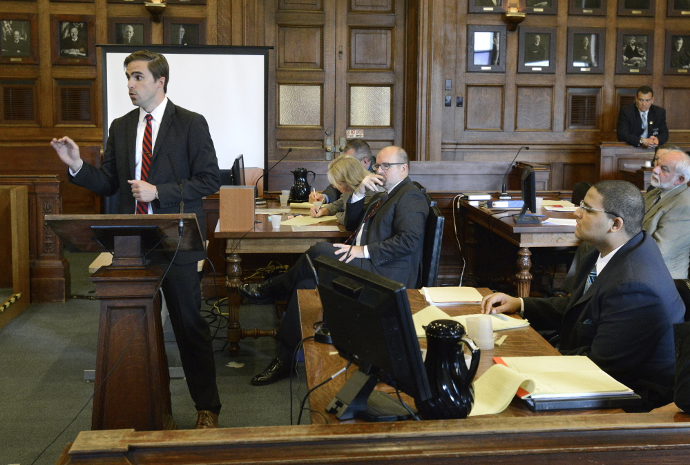 Defense attorney Dylan Boyd makes his opening statement to the jury in the murder trial of Anthony Pratt Jr. (seated lower right) at the Cumberland County Court House in Portland. Assistant Attorney General Donald Macomber listens in background.