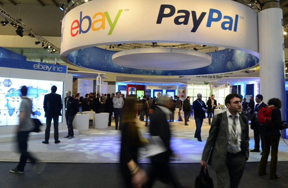 In this Wednesday, Feb. 27, 2013, file photo, attendees walk in front of an EBay and PayPal display area at the Mobile World Congress, the world's largest mobile phone trade show, in Barcelona, Spain.