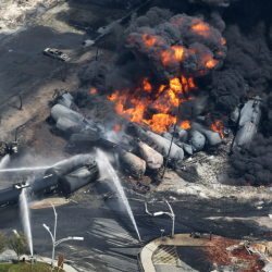 Smoke rises from railway cars carrying crude oil that derailed in downtown Lac-Megantic, Quebec, in July 2013. That was the worst of recent oil train accidents that have prompted proposed new safety rules.