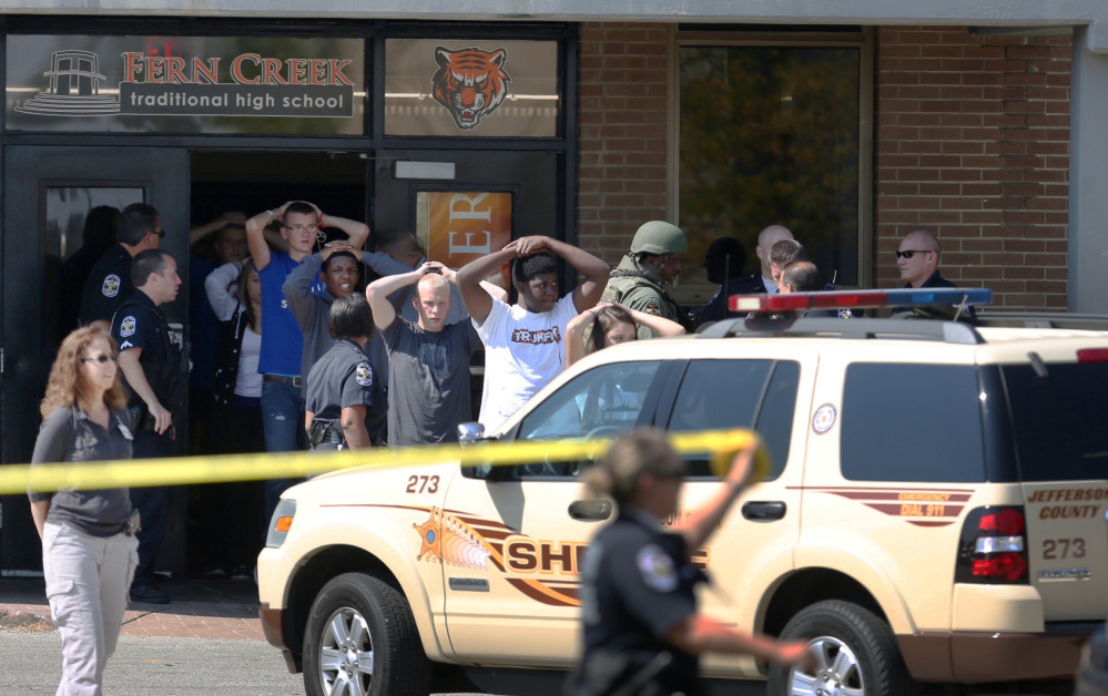 Students put their hands on their heads as they are out of Fern Creek High School in Louisville, Ky., on Tuesday.