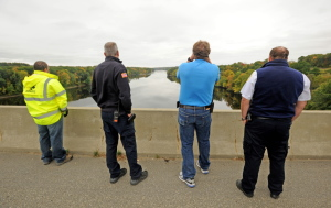 Lt. Scott Holst, right center, with the Waterville Fire Department spots a woman who jumped from Carter Memorial Bridge into the Kennebec River from the bridge on the Winslow and Waterville town line just before 2pm on Tuesday.