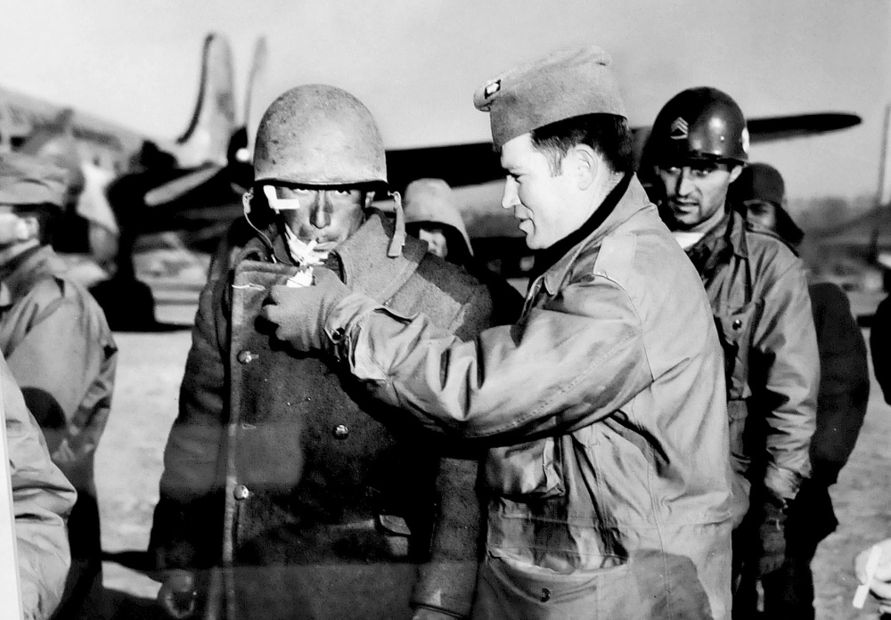 A photograph by Galen Leavitt shows an officer lighting the cigarette of a wounded soldier during the Korean War.