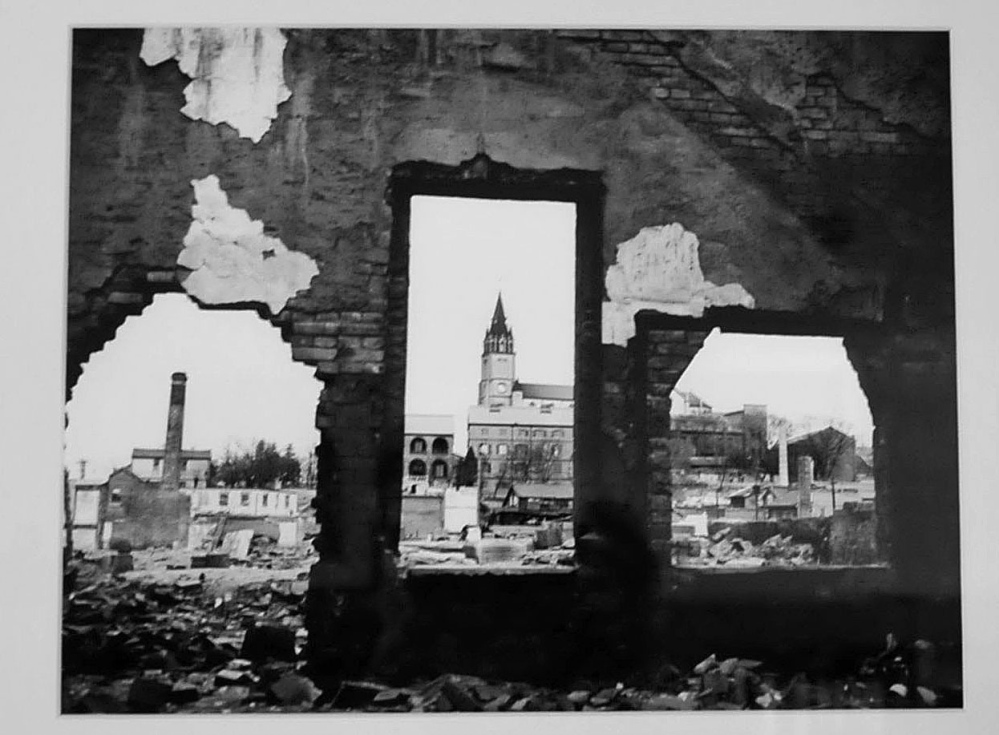 A church in background is seen through the bombed remains of a home in Korea and part of an photo exhibit taken by Galen Leavitt. It is on exhibit at the Oakland Library beginning Wednesday.
