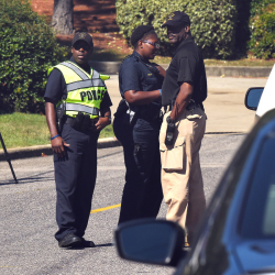 Police officers confer near the scene where three people were killed, including the gunman, at a UPS facility in Birmingham, Ala., on Tuesday. The Associated Press