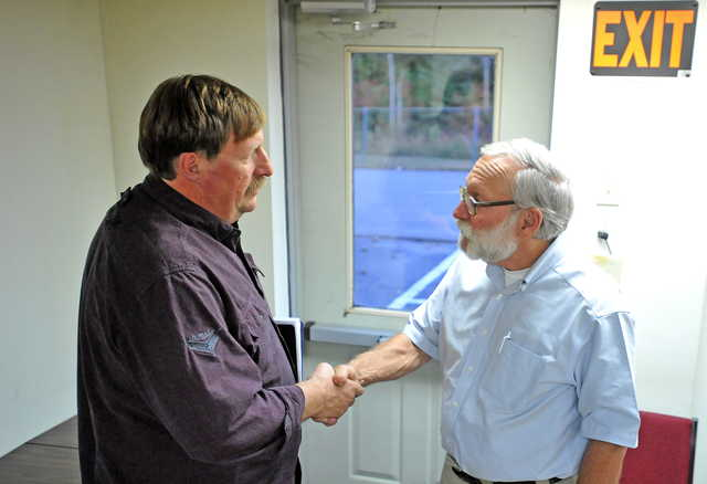 Mike Perkins, left, says farewell to Peter Nielsen, Oakland town manager, after a town meeting at the Oakland town office on Wednesday.