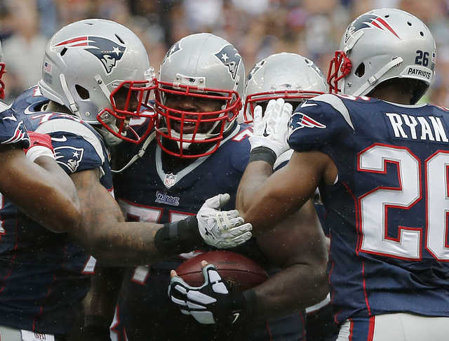 New England Patriots defensive tackle Dominique Easley, left, and cornerback Logan Ryan (26) congratulate defensive tackle Vince Wilfork, center, on his interception in the fourth quarter Sunday against the Oakland Raiders in Foxborough, Mass. The Patriots won 16-9.