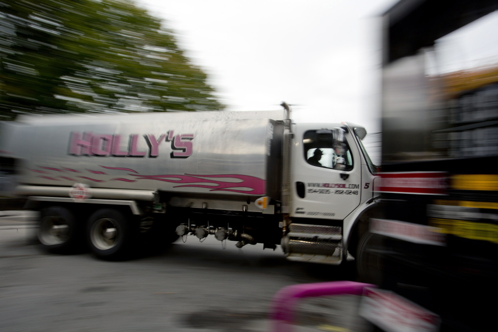 An oil delivery truck moves past a gas pump Wednesday at Holly's Super Gas on Main Street in Westbrook. Increased domestic production of crude oil has driven down the average price of home heating oil in Maine to $3.32 per gallon, the lowest in more than two years, according to a survey.