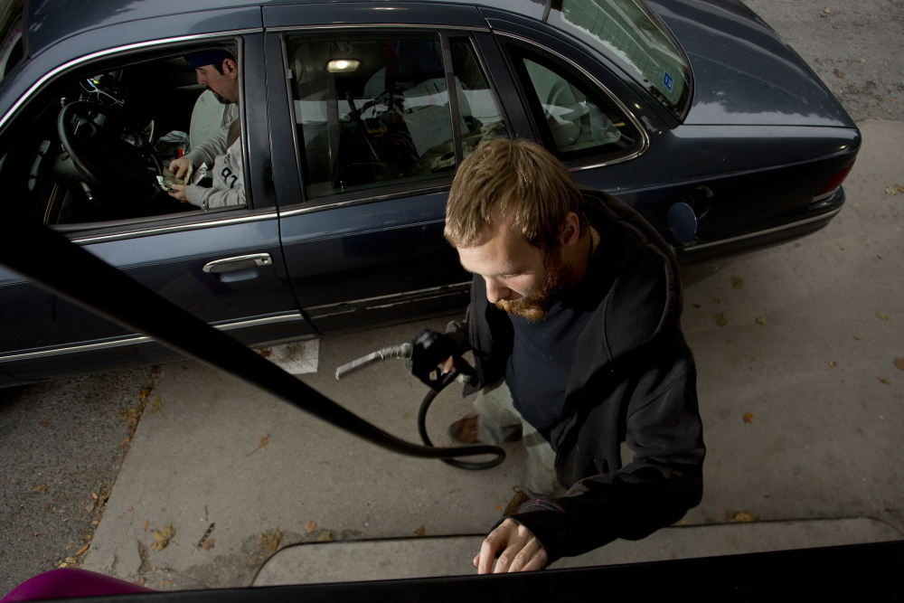 Paul Berg prepares to pump gas for a customer at Holly's Super Gas. The average price of gas has fallen to $3.43 per gallon – down more than 30 cents since spring – and nationally may be as low as $3.10 by December.