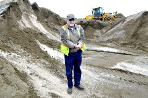 Winslow Public Works Director Paul Fongenie holds a handful of winter road salt Wednesday as employee Tony Rossignol mixes salt and sand at the Winslow department.