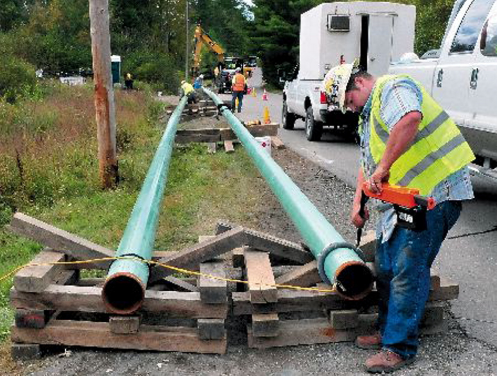 Jeremy Clubbs, of subcontractor U.S. Pipelines, works to install gas pipeline sections in September 2013 outside the Sappi paper mill in Skowhegan. Operators of central Maine's paper mills say access to natural gas is critical to controlling energy costs.