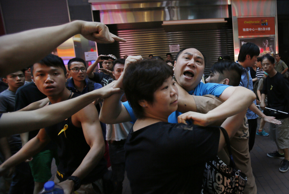 An instigator is taken from the crowd by pro-democracy student protesters after a scuffle with local residents in Mong Kok, Hong Kong, Saturday.