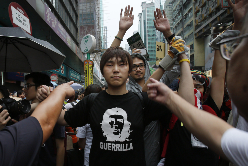 A pro-democracy student protester stands firm as he is insulted by local residents in Mong Kok, Hong Kong, Saturday.
