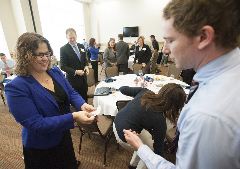 Emily Cain hands out business cards to Matt McLaughlin in September during a candidate luncheon for Fusion Bangor, a business organization, at the Cross Insurance Center in Bangor.