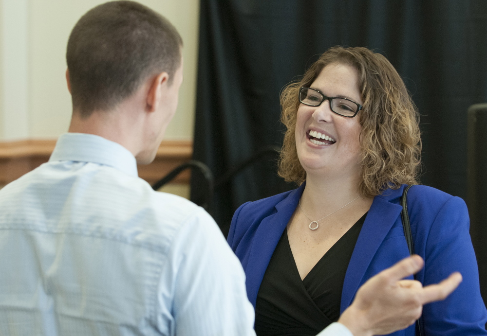 Emily Cain talks with Jonathan Bench during a candidate luncheon in September for Fusion Bangor, a business organization, at the Cross Insurance Center in Bangor.