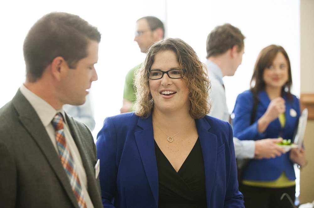 Emily Cain talks with Matt Cobb during a candidate luncheon for Fusion Bangor, a business organization, in September at the Cross Insurance Center in Bangor.
