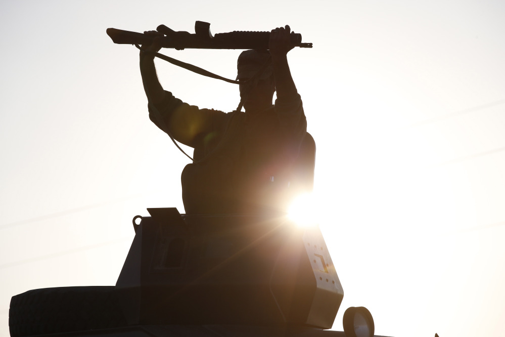 A Turkish soldier adjusts his rifle atop of an armoured vehicle as it moves to its new position at Mursitpinar near Suruc, at the Turkey-Syria border, Sunday as fighting intensified between Syrian Kurds and the militants of Islamic State group in Kobani.