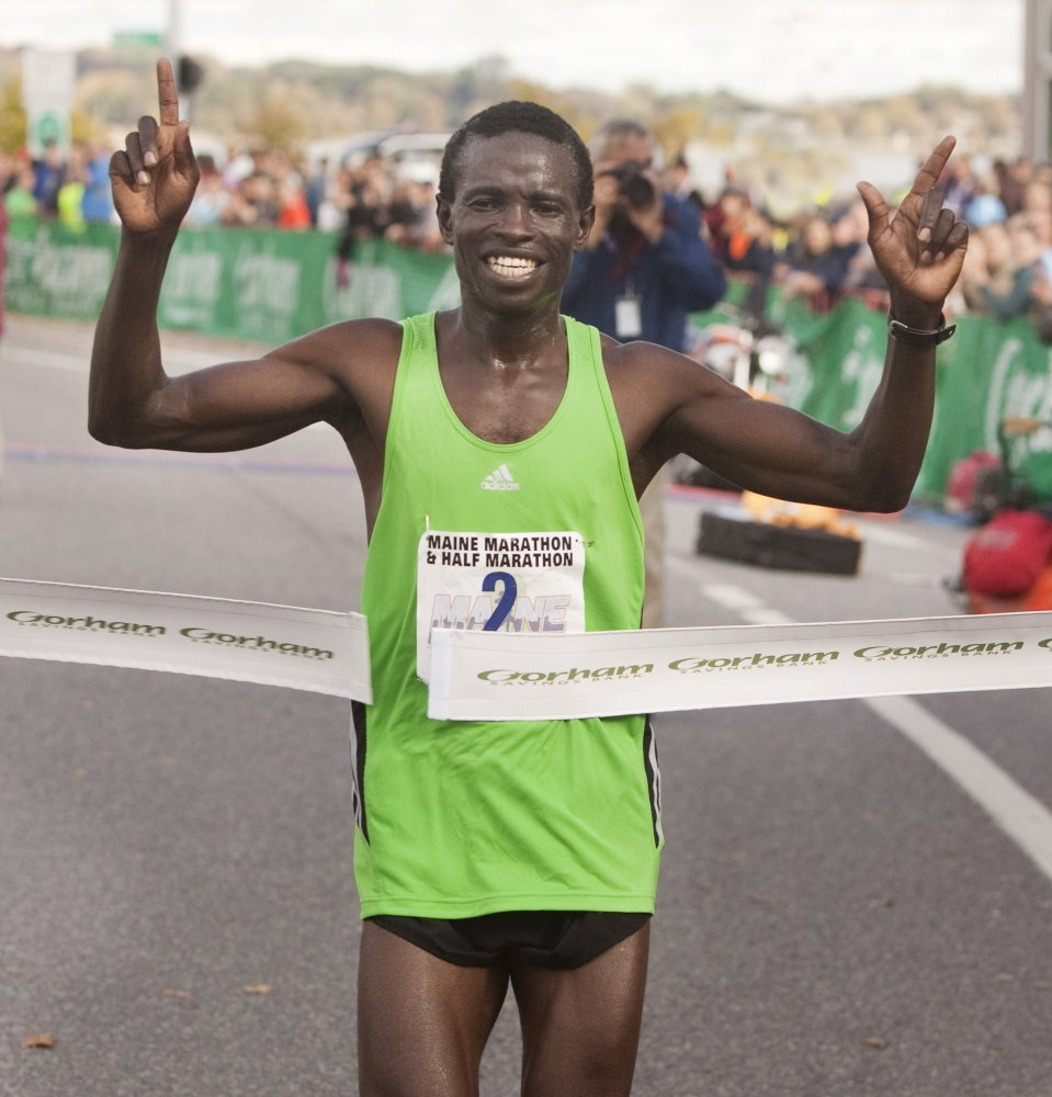 Moninda Marube of Auburn celebrates as he crosses the finish line winning the Maine Marathon in Portland on Sunday.