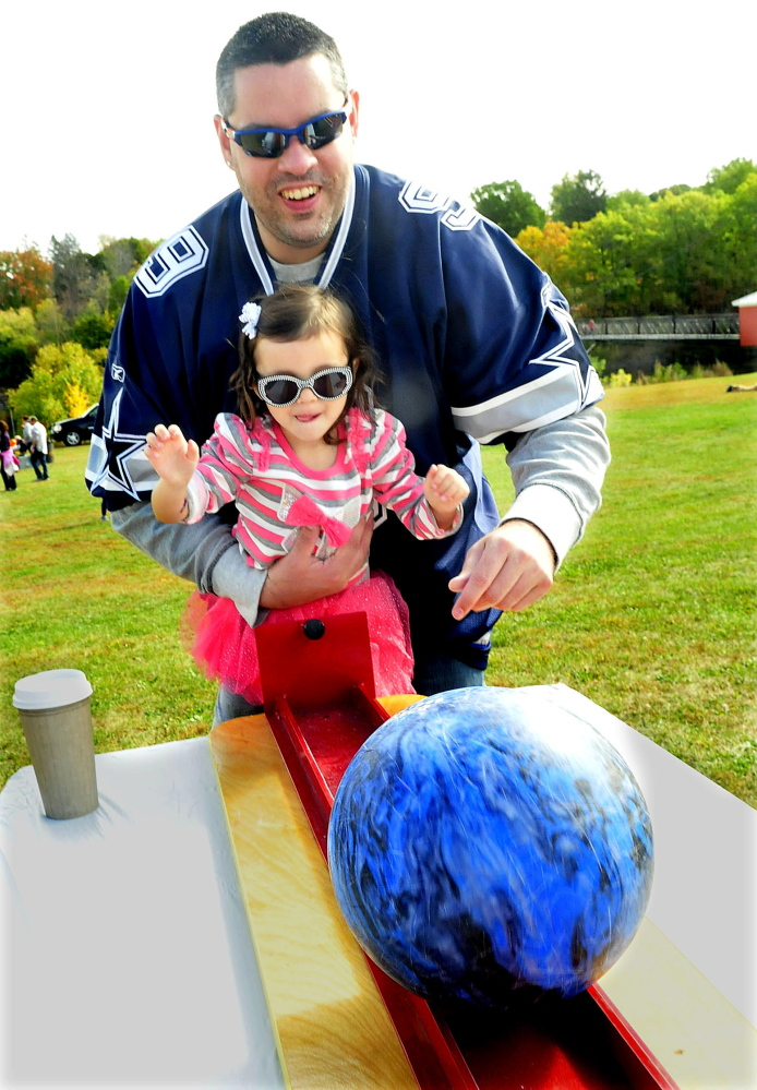Jimmy Peters helps his daughter Maci with a bowling ball event that was part of the Harvest Festival children games in Waterville on Sunday.