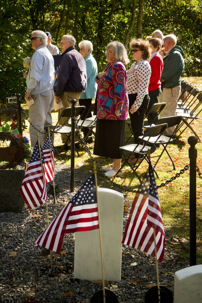 People pledge the flag at Grand Trunk Cemetery in Portland during a dedication of a memorial stone for the early settlers of East Deering.