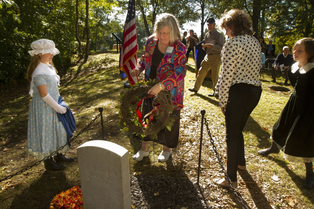 Theresa Sawyer Cobb places a wreath near a memorial stone for the early settlers of East Deering Village being dedicated at Grand Trunk Cemetery in Portland on Sunday. Theresa's sixth grandfather was Anthony Sawyer, who was one of those settlers and is buried in the cemetery.